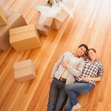 A man and woman take a moment to relax on the floor while packing up their belongings into cardboard boxes.