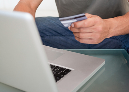 A man holds his credit card while using the laptop computer to pay a bill online.