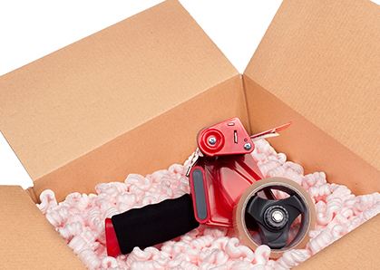 An opened box filled with packing popcorn and topped with a packing tape dispenser.
